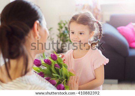 Mothers day, little girl giving flowers to her mum - stock photo