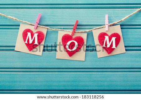 Mothers day message on felt hearts over blue wooden board - stock photo
