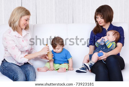 Mothers feeding babies on the soda in the room - stock photo