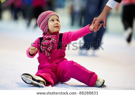 Mothers hand help little cute girl on the rink