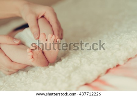 mothers hands holds baby feet at white blanket