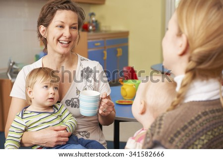 Mothers With Babies Chatting And Drinking Coffee At Playgroup - stock photo