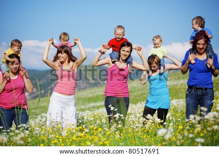 Mothers with children in flower field - stock photo