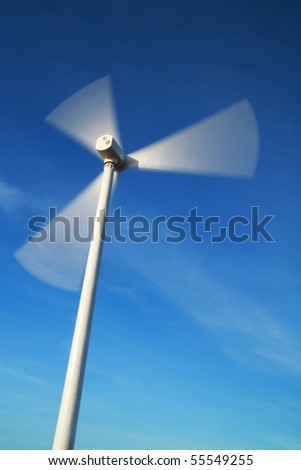 motion blade of modern win turbine in windy day with blue sky. - stock photo