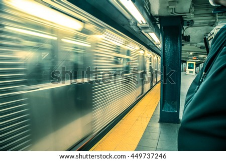 Motion blur as New York City subway train speeds through station with person waiting on the platform - stock photo