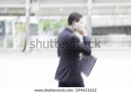 motion blur businessman on phone walking to work - stock photo
