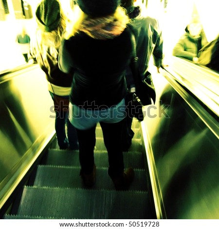 Motion blur, high key picture of people going down the escalator - stock photo