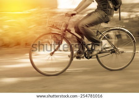 Motion blur. Male cycling bicycle. Vintage filter. - stock photo
