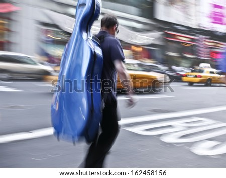 motion blur man on a city street with a musical instrument
