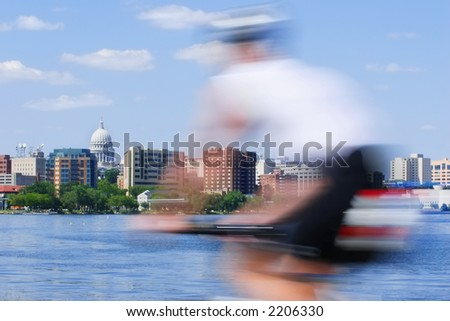 Motion Blur of a person riding a bicycle past the capitol city of Wisconsin in Madison - stock photo