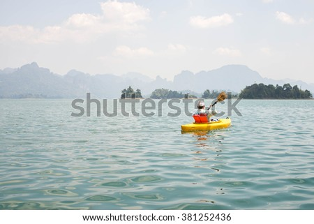 Motion blur of Asia man paddling in Chiewlarn dam in Surat Thani, Thailand