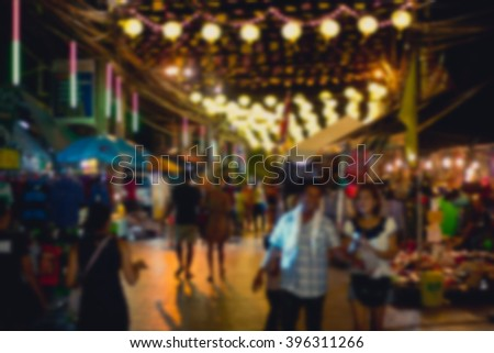 motion blur of many people shopping in shopping night street market - stock photo