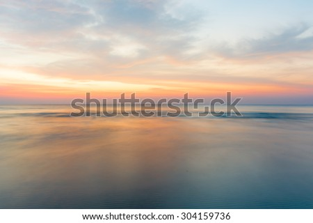 Motion blur of the sea under twilight sunset sky with long exposure effect. - stock photo