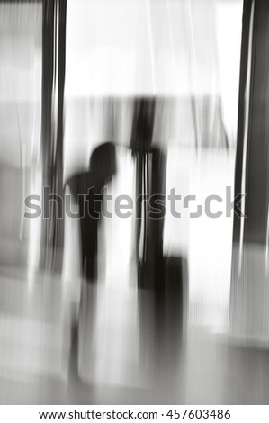 Motion blur of two shadows of people talking in doorway. - stock photo