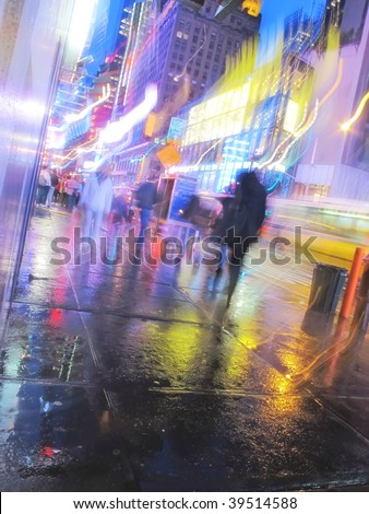 Motion blur ? people walking at Times Square, New York, at night in rainy weather - stock photo