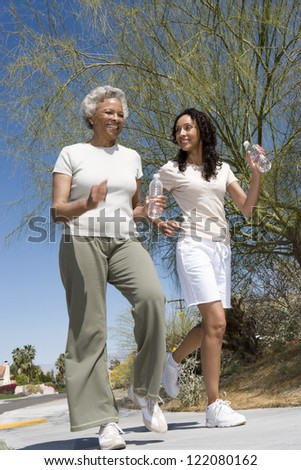 Motion blur shot of an African American mother and daughter jogging together in park - stock photo