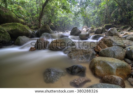 motion blur shot of river stream with boulders in deep tropical forest