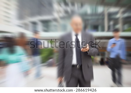 motion blur suit and tie businessman hand on mobile phone walking to work - stock photo