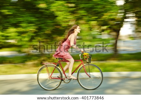 motion blur. young woman in a dress rides a bike in a summer park - stock photo