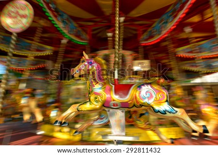 Motion blurr of vintage horse of amusement ride on merry-go-round carousel.  Amusement concept - stock photo