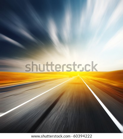 Motion blurred asphalt road and blurred sky with clouds - stock photo