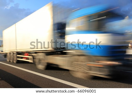 Motion blurred blue truck on highway - stock photo