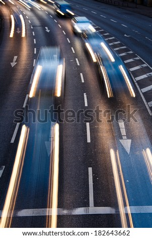 Motion blurred city road traffic (color toned  image) - stock photo
