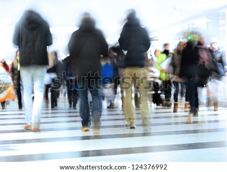 Motion blurred crowd. Intentional high key and motion blur. - stock photo