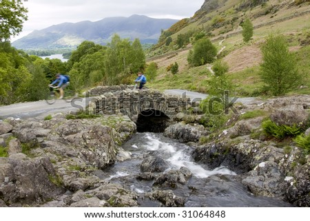 Motion Blurred Cyclists Crossing Ashness Bridge, Lake District England - stock photo