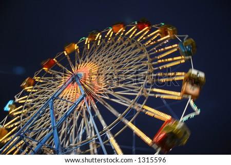 Motion Blurred Ferris Wheel at Night - stock photo
