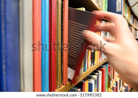 Motion blurred hand picking book in library bookshelf - stock photo