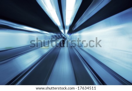 Motion blurred people travelling on a travolator walkway late at night - stock photo