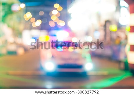 Motion blurred police car with lights turned on at night city - stock photo