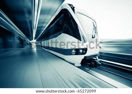 Motion blurred public rapid train near station - stock photo