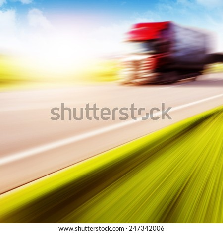 Motion blurred red truck on highway at sunset. - stock photo