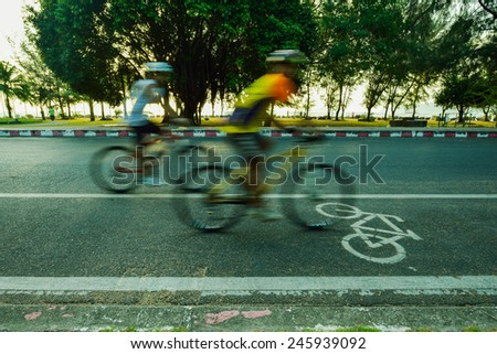 Motion blurred silhouette a part of cyclist going fast on a bike lane - stock photo