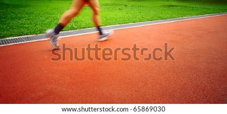 Motion blurred sportsmen running on red stadium's track - stock photo