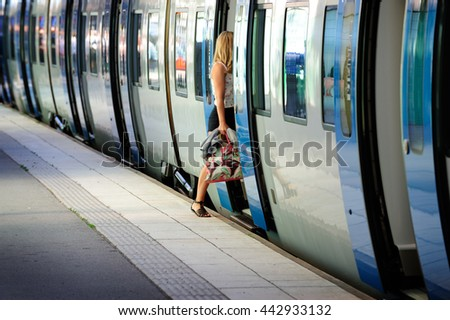Motion blurred young woman enters (subway) train