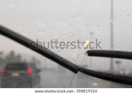 Motion of windscreen wipers removing rain drops water on windshield with blurred traffic on road background during hard rainy day - stock photo