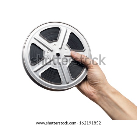 Motion picture film reel in man's hand - stock photo