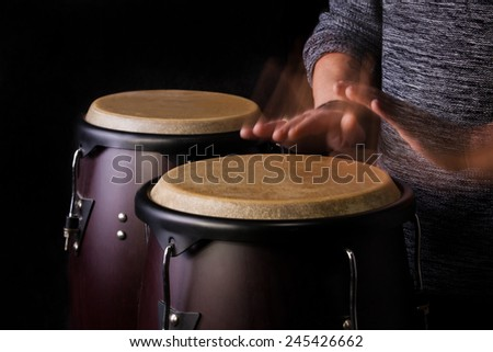 Motion Picture of a bongo Player. Black background.Picture is toned. - stock photo