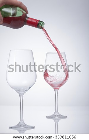 Motion picture of a man hand fill a glass with wine. One empty glass stand in front. Against a white background and a vignette. - stock photo