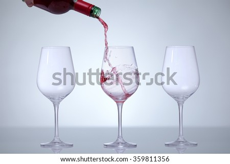 Motion picture of a man hand fill a glass with wine.Three glasses in a row. Against a white background and a vignette. - stock photo