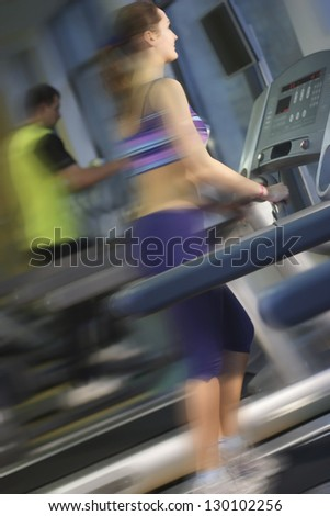 motion woman running in gym on automatic track machine