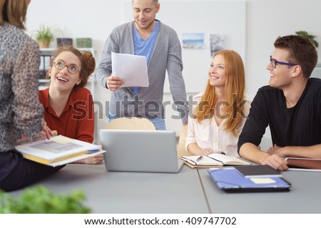 Motivated diverse young business team having a meeting grouped around a laptop computer and engaging in animated discussion of their project - stock photo