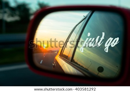 Motivation quote Just go with Sunset reflection in the rear view mirror of a car on a highway - stock photo