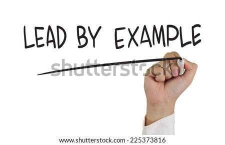 Motivational concept image of a hand holding marker and write Lead by example isolated on white - stock photo