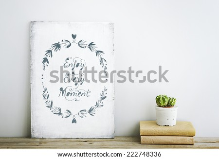 motivational inspirational poster quote ENJOY EVERY MOMENT on the white wall. American or Scandinavian style room interior.  - stock photo