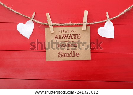 Motivational message with hearts and clothespins on red wood - stock photo