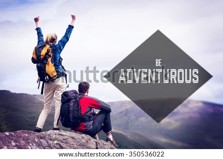 Motivational new years message against excited couple reaching the top of their hike - stock photo